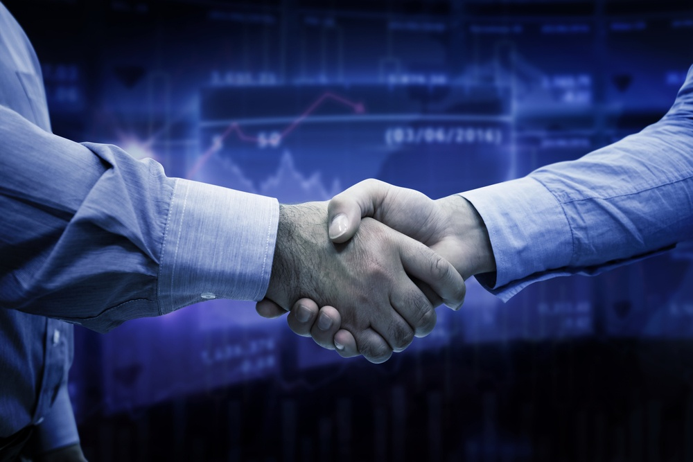 Men shaking hands against stocks and shares.jpeg