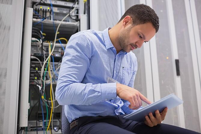 Man using tablet pc beside servers in data center.jpeg