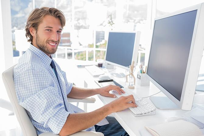 Smiling designer working at his desk in modern office.jpeg
