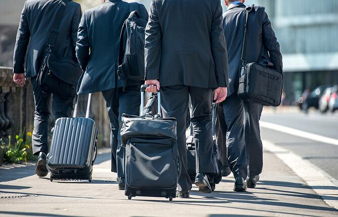 A group of businessmen pulling suitcases with luggage.jpeg