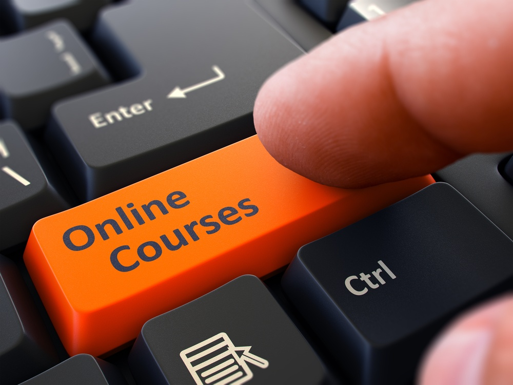 Online Courses Orange Button - Finger Pushing Button of Black Computer Keyboard. Blurred Background. Closeup View..jpeg