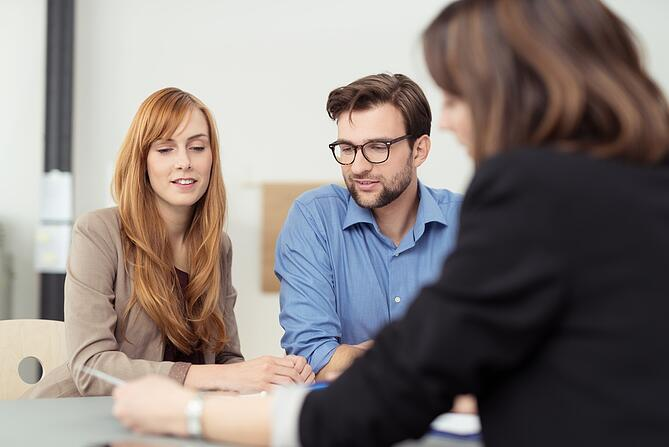 Broker making a presentation to a young couple showing them a document which they are viewing with serious expressions