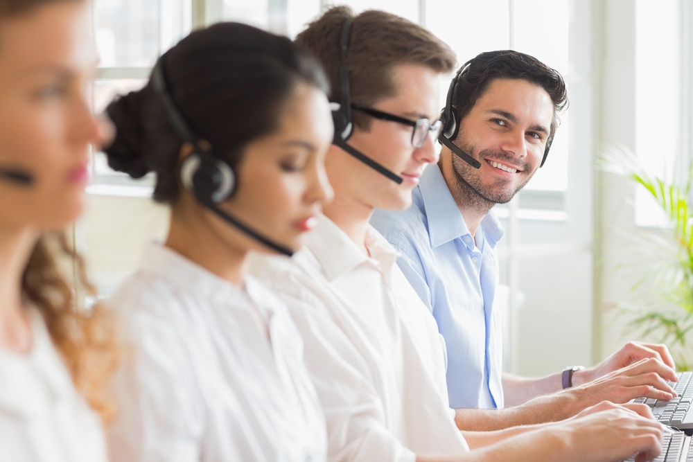 Portrait of happy businessman with colleagues working in call center
