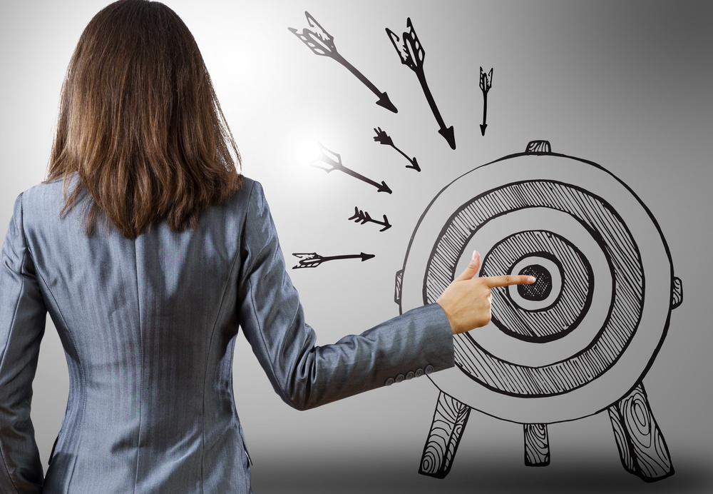 Rear view of businesswoman pointing at drawn target.jpeg
