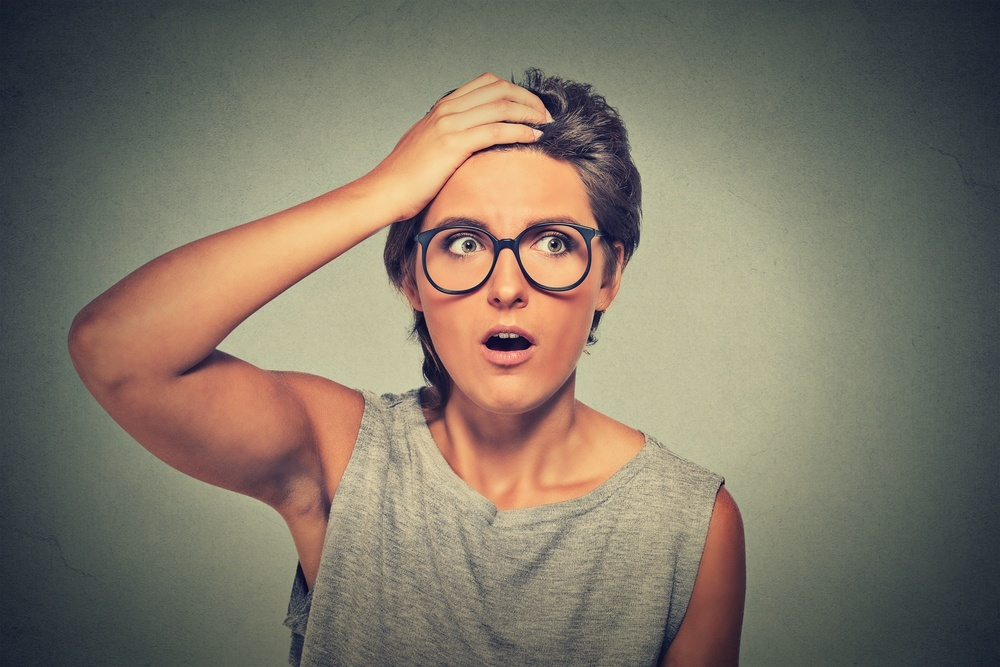 Surprise astonished woman. Closeup portrait woman with glasses looking surprised in full disbelief wide open mouth isolated grey wall background. Human emotion facial expression body language.-1