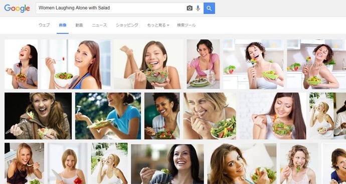 サラダを前に1人で笑っている女性